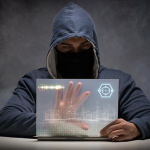 Man in black hooded sweatshirt with mask hacking a computer