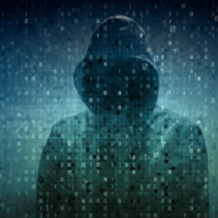 hacker in the shadows behind computer code